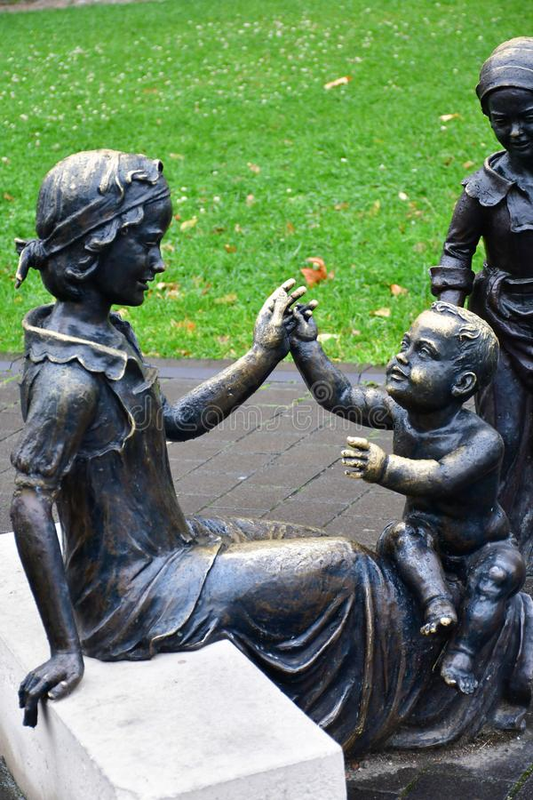 Statue en bronze de femme et d'enfants images stock