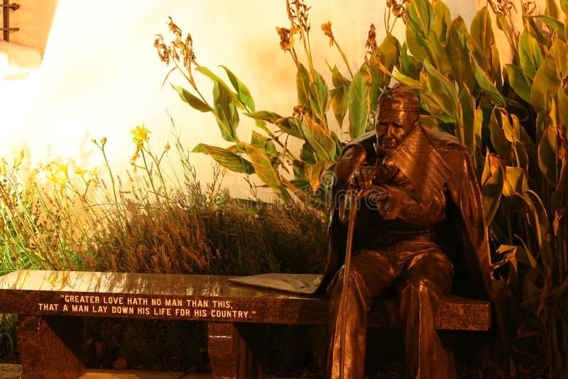 Statue en bronze de vétéran sur le banc la nuit photographie stock