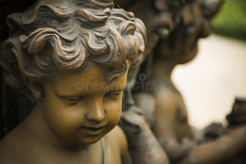 Statue en bronze du visage d'un enfant d'une chevelure bouclé photos stock