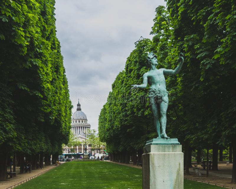 Statue entre les arbres avec le Panthéon dans la distance, aux jardins du Luxembourg à Paris, la France photos libres de droits