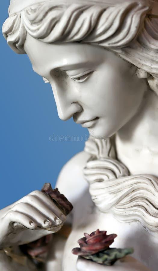 Statue femelle jugeant une rose disponible photographie stock