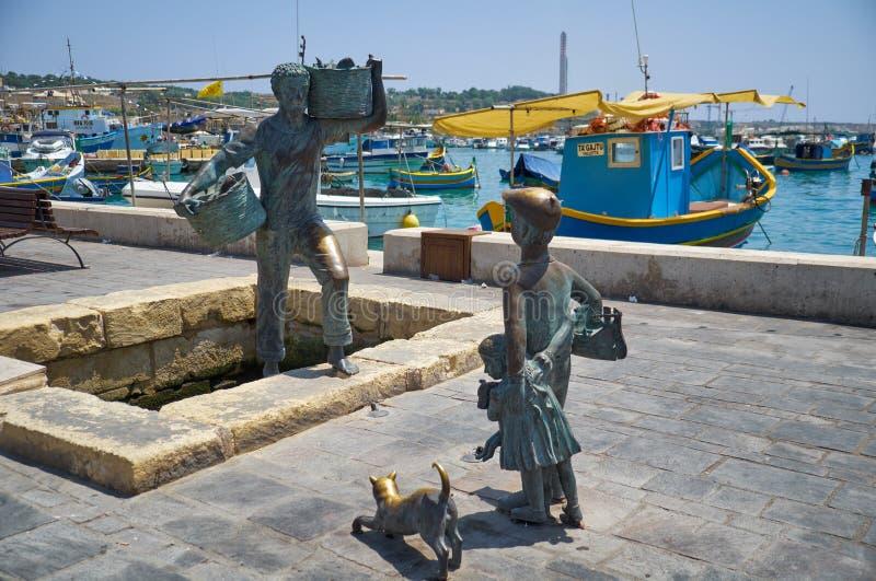 The statue of the fishermen on the harbour of village Marsaxlokk. Malta. MARSAXLOKK, MALTA - AUGUST 2, 2015: The bronze statue of the fishermen on the harbour of royalty free stock image