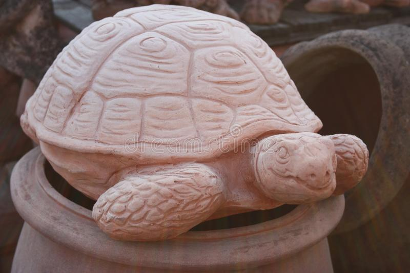Statue in the form of a large earth tortoise or large tortoise. artistic work of a ceramic sculptor and worker. representation of. An animal by a craftsman stock photography