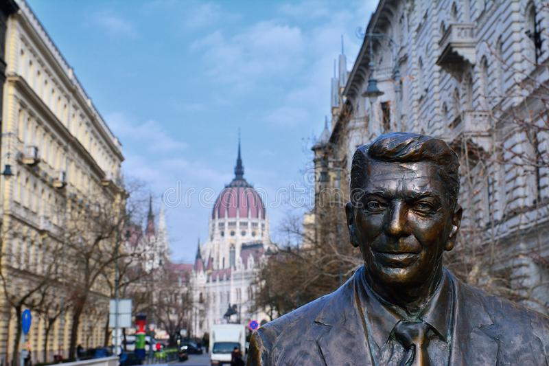 Statue of the former U.S. President Ronald Reagan on the background of Hungarian Parliament Building. Budapest, Hungary - March 28, 2018: Statue of the former U royalty free stock photo