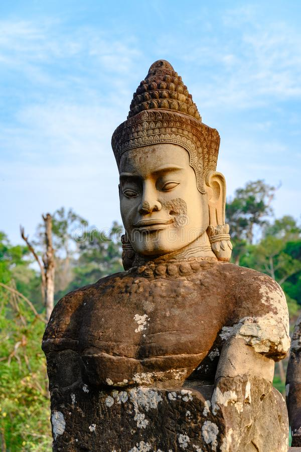 Statue of smiling face on South Bridge to Entrance of Angkor Thom, Khmer styled Temple, Siem Reap, Cambodia. Rebuild of a smiling face in Angkor Thom. Angkor stock photography
