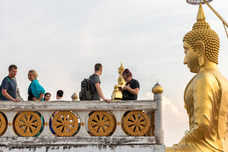Statue of golden Buddha looks on tourists in the Wat Tham Suea Tiger cave temple royalty free stock photo