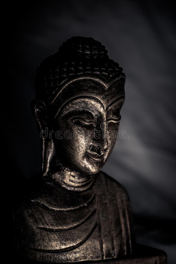 The statue of a half Buddha statue in the shadows. Light, ancient, architecture, art, asia, asian, background, beautiful, believe, black, buddhism, buddhist royalty free stock image