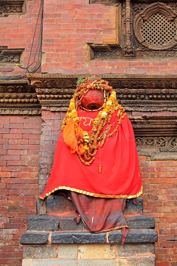 Statue Of Hamunan outside Sundari Chowk in Patan, Nepal. PATAN, NEPAL - APRIL 2014 : Statue Of Hamunan painted in red paste and cloaked in red fabric sitting royalty free stock photo