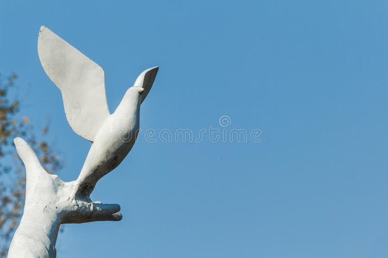 The statue of hands and pigeons. A hand is held doves, symbol of the human infinite yearning for peace and happiness life. White pigeon standing on the hands, on royalty free stock photo