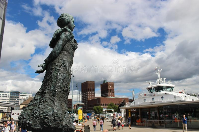Statue in the harbor Pipervika in Oslo, Norway, Europe. View on the harbor and the City Hall. Photo taken in August 2015 royalty free stock photography