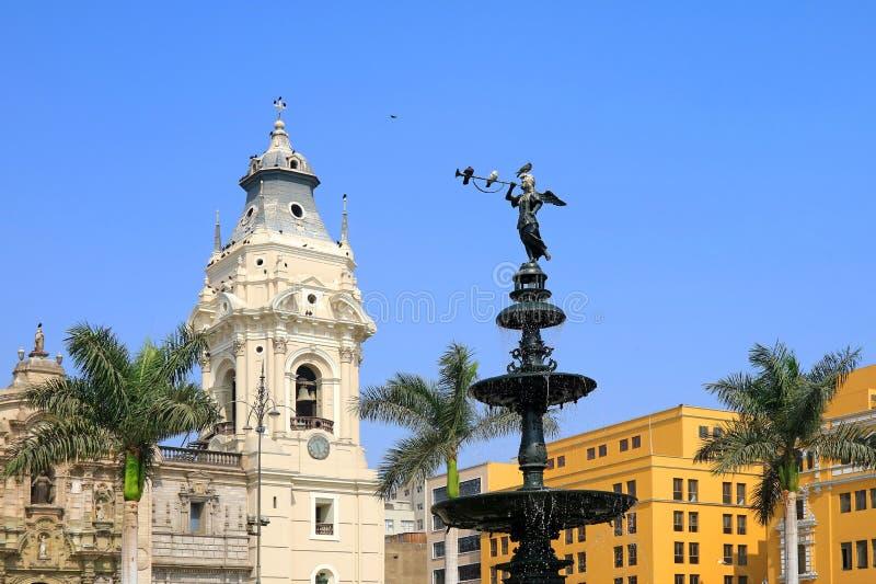 Statue historique de l'ange de la renommée sur la fontaine au maire de plaza avec la cathédrale de basilique de Lima dans le cont photo stock