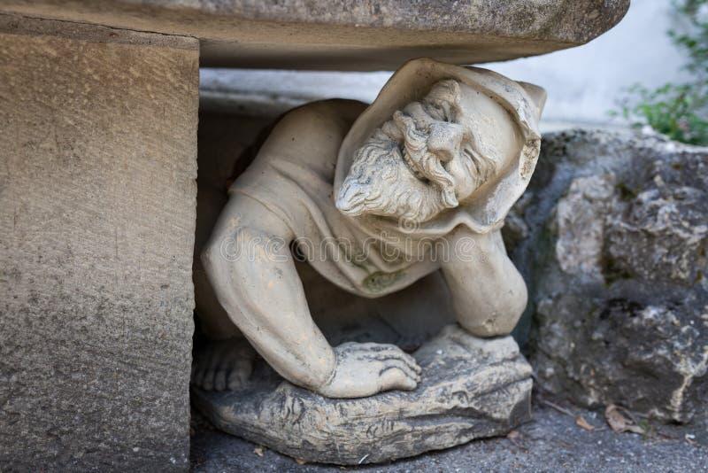Statue humaine drôle se tapissant sous le banc dans le jardin images libres de droits