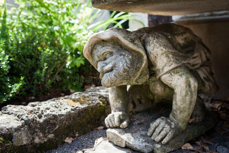 Statue humaine drôle se tapissant sous le banc dans le jardin photos libres de droits