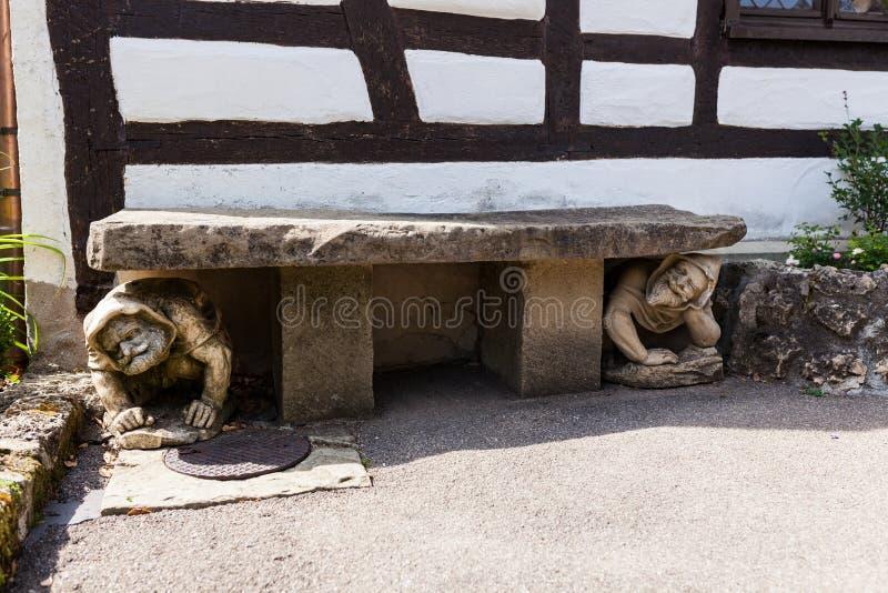 Statue humaine drôle se tapissant sous le banc dans le jardin images stock