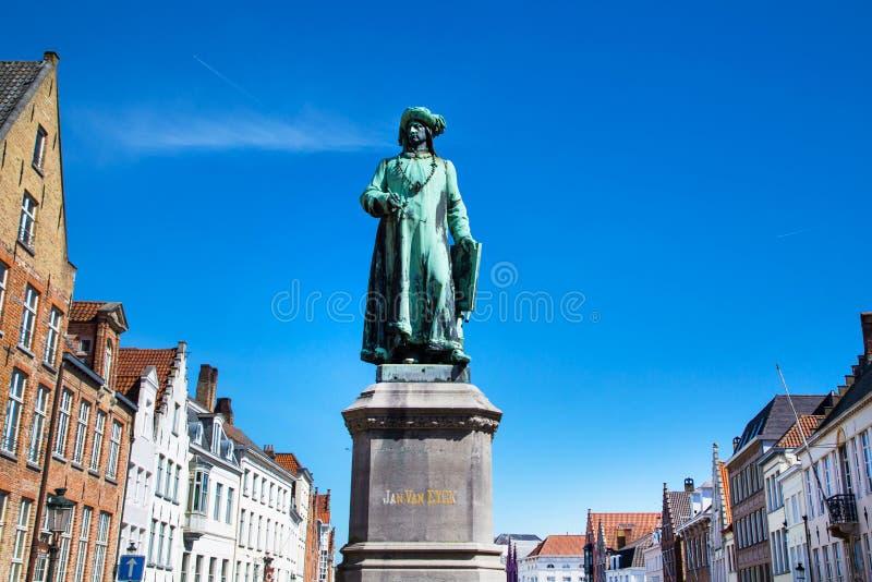 Statue of Jan Van Eyck and medieval house exterior against blue sky in Brugge, Belguim stock photos