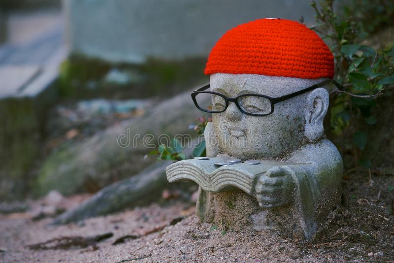Statue of Jizo, Japan. A statue of Jizo, the Buddhist child monk protector of children, travelers and women, Japan. This one is wearing glasses, wearing a little royalty free stock photos