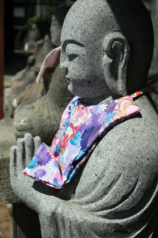 Statue of Jizo with scarf, Japan. A statue of Jizo, the Buddhist child monk protector of children, travelers and women, Japan royalty free stock photo