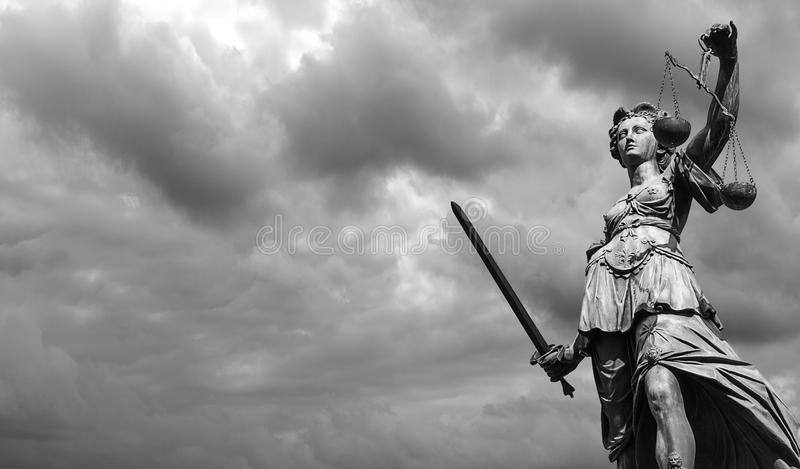 Statue of justice goddess Justitia with cloudy sky, Black and. Lady Justice Statue against dramatic cloudy sky. ideal for websites and magazines layouts royalty free stock images
