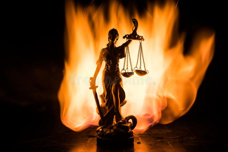 The Statue of Justice - lady justice or Iustitia / Justitia the Roman goddess of Justice on a dark fire background. Selective focus royalty free stock photo