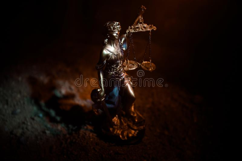 The Statue of Justice - lady justice or Iustitia / Justitia the Roman goddess of Justice on a dark fire background. Selective focus stock images