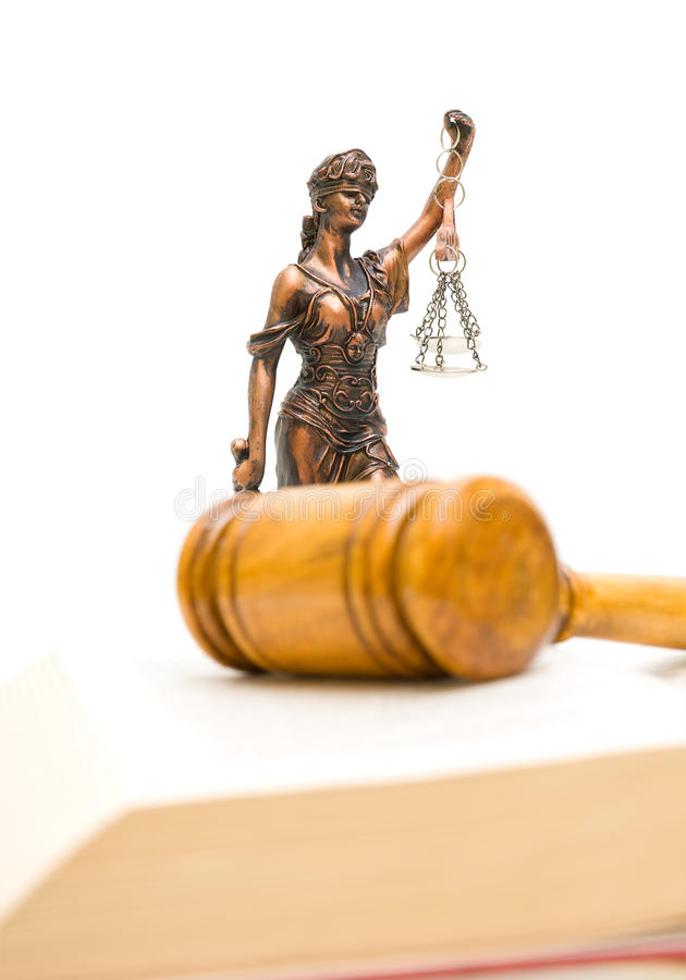 Statue of justice on a white background. vertical photo. Statue of justice on a white background. Gavel and law book in the foreground out of focus. vertical stock photography