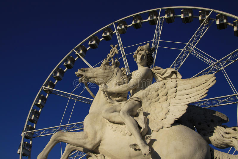 Statue of King of Fame riding Pegasus on the Place de la Concorde with ferris wheel at background, Paris, France. Statue of King of Fame riding Pegasus on the stock photography