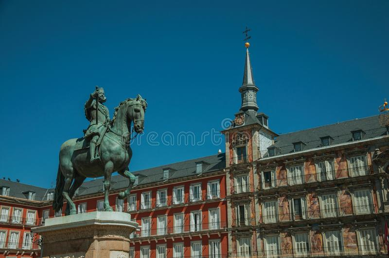 Statue of King Philip III at the Plaza Mayor square in Madrid. Bronze equestrian statue of King Philip III at the Plaza Mayor square and old buildings, in a stock photo