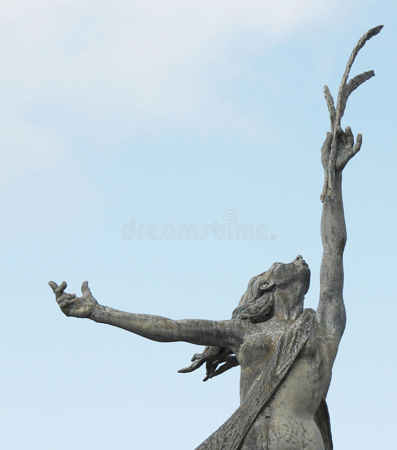 Statue of a lady holding a tree branch royalty free stock images