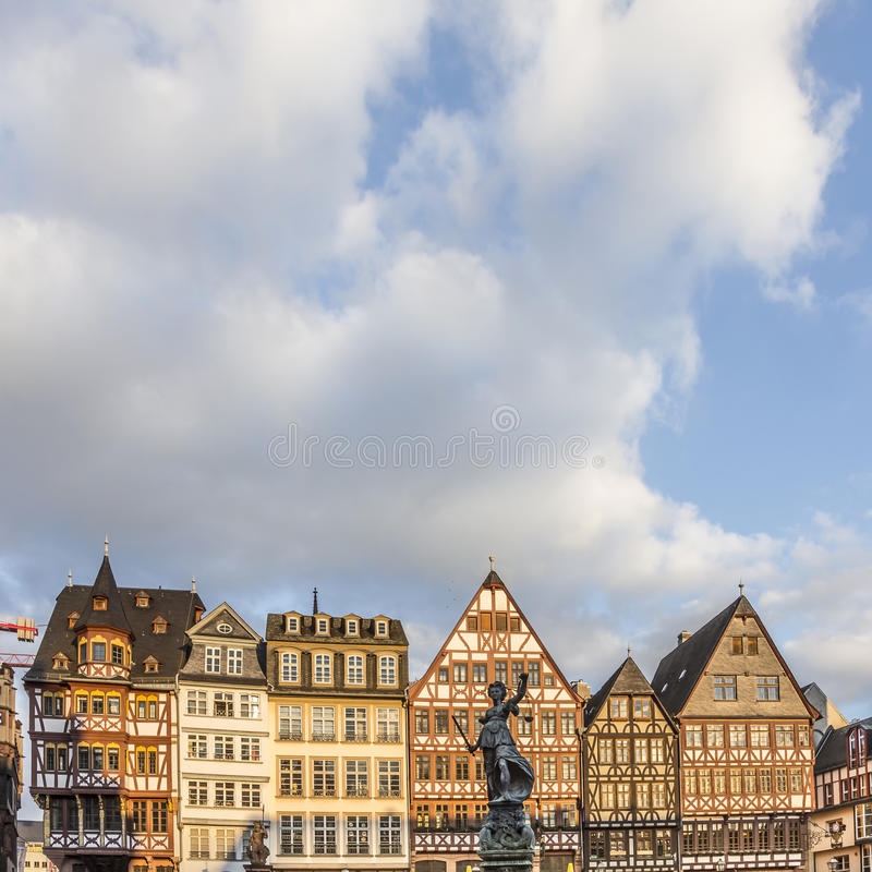 Statue Lady Justice stands at the Roemerberg. FRANKFURT, GERMAY - FEB 22, 2015: statue Lady Justice with sword and scale stands in front of half timbered houses stock images