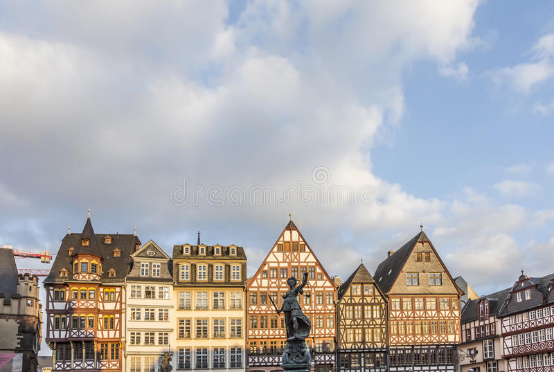 Statue Lady Justice stands at the Roemerberg. FRANKFURT, GERMAY - FEB 22, 2015: statue Lady Justice with sword and scale stands in front of half timbered houses royalty free stock image