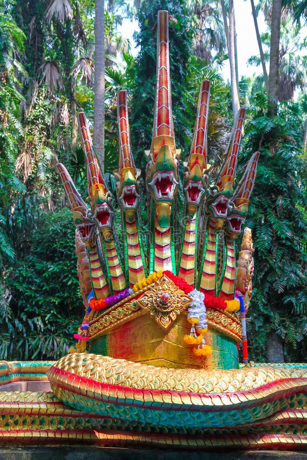 Statue of a large green Naga serpent with golden fins, with seven heads. stock image