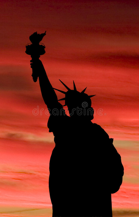 The statue of liberty as a silhouette against a brilliant fiery stock photos