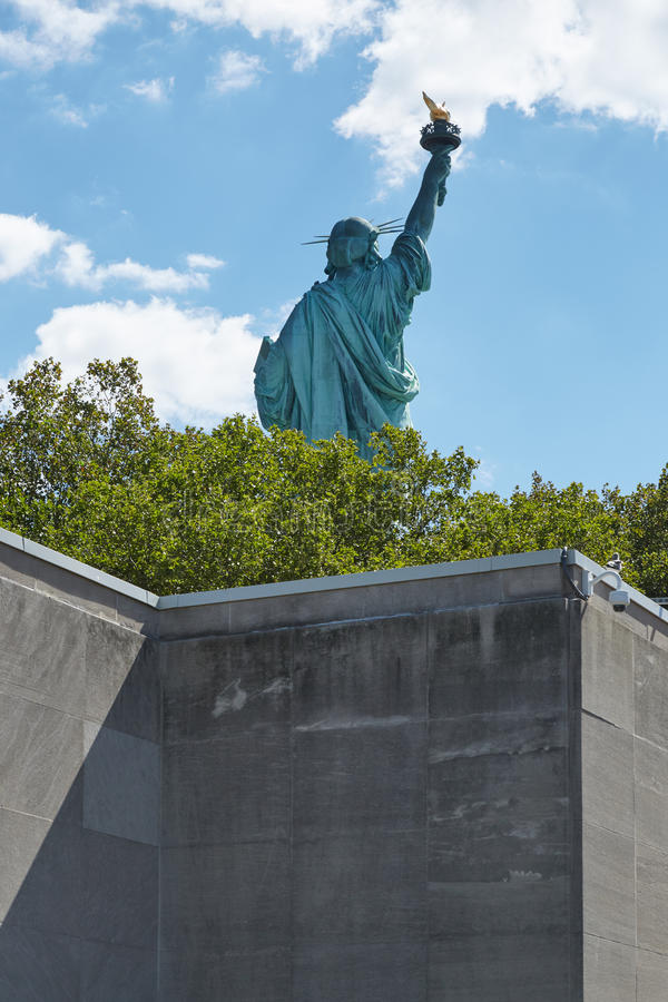 Statue of Liberty back seen behind a wall, sunny day stock photography