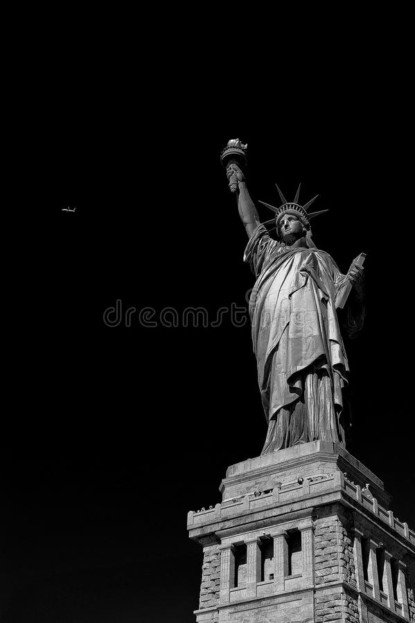 Statue of Liberty with black background and airplaine. Scenic view of Statue of Liberty, New York city harbor, U.S.A stock photography
