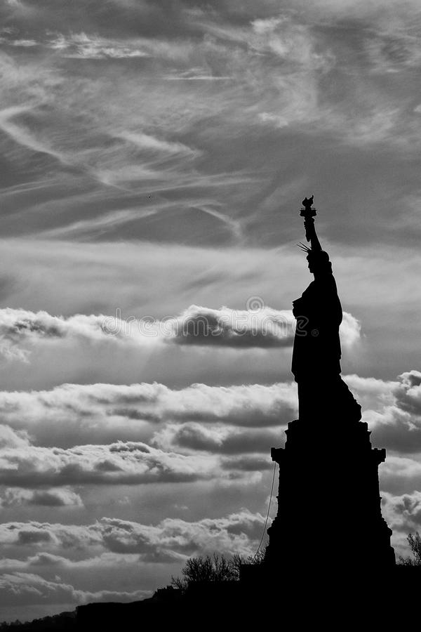 Statue of liberty black and white vertical isolated silhouette. New York statue of liberty black and white vertical isolated silhouette on cloudy sky royalty free stock images