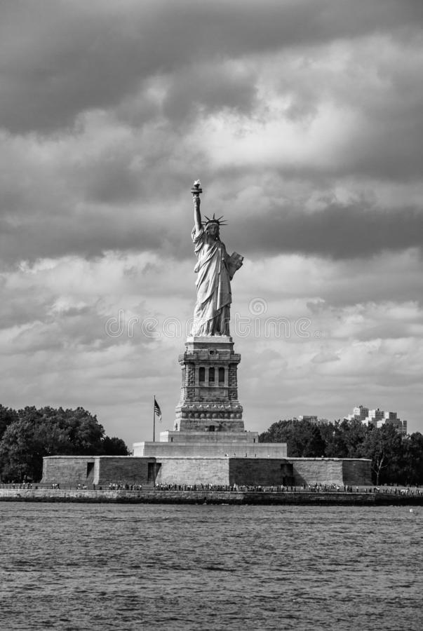Statue of Liberty with her plinth - Portrait Aspect - Black and White. The iconic statue of liberty in New York, USA, as viewed from the Staten Island Ferry royalty free stock image