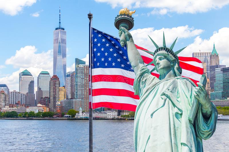 Statue of Liberty with a large american flag and New York skyline in the background royalty free stock photo