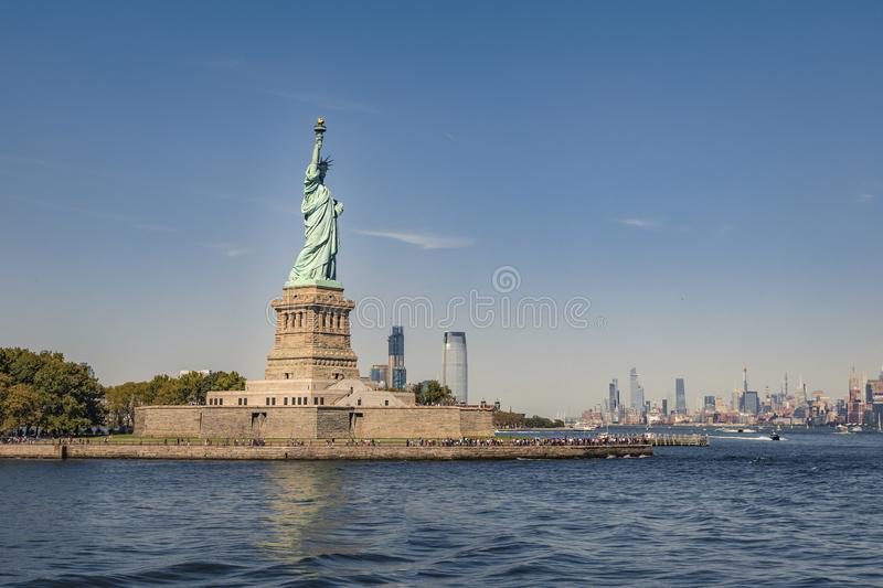 Statue of Liberty with Manhattan skyline panoramic view on a clear blue day royalty free stock image