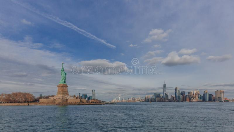 Statue of Liberty overlooking buildings of downtown Manhattan by water, in New York City, USA royalty free stock photography