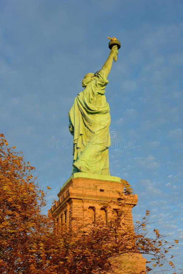 The Statue of Liberty seen from the side with warm afternoon sun, fall trees and blue cloudy sky.  royalty free stock photos