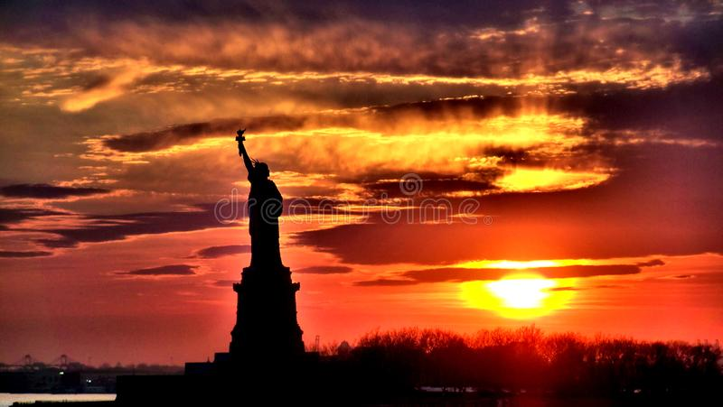 The Statue Of Liberty Silhouette At Sunset. The Statue Of Liberty Silhouette Under A New York City Sunset royalty free stock images