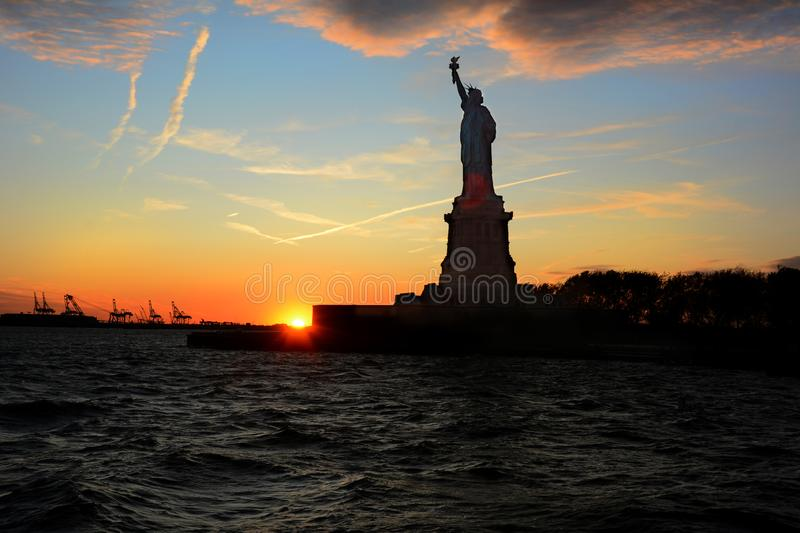 Statue of Liberty in silhouette at sunset viewed from the water with clouds and colorful sky.  stock photos