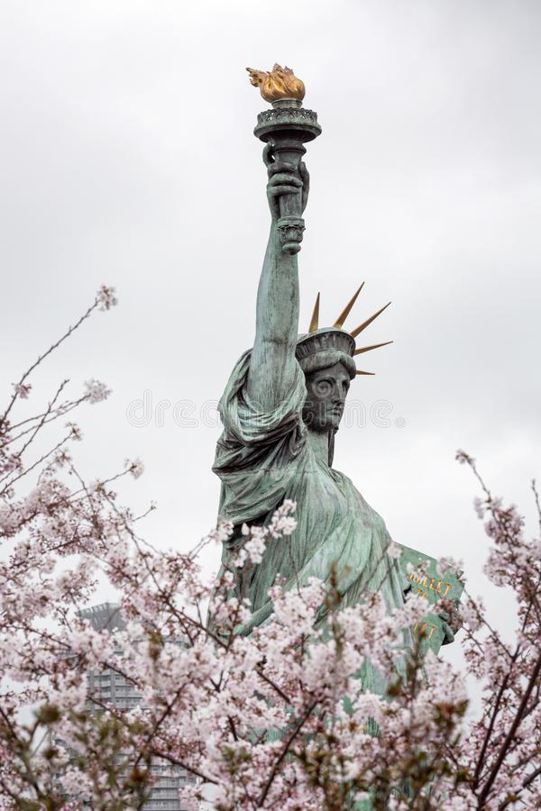 Statue of Liberty in Tokyo on the island of Odaiba in blooming sakura on a gloomy day. Vertical royalty free stock photos