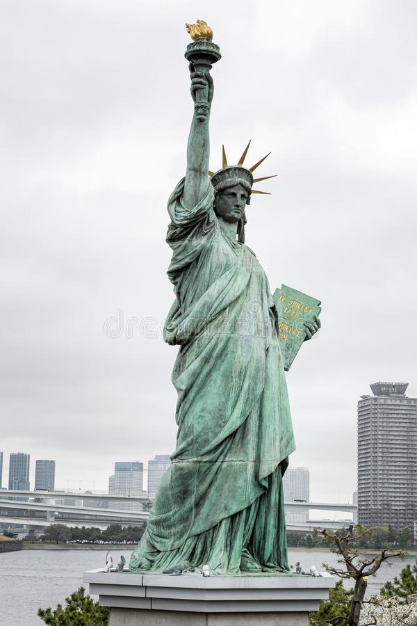 Statue of Liberty in Tokyo on the island of Odaiba in blooming sakura on a gloomy day. Vertical stock photography
