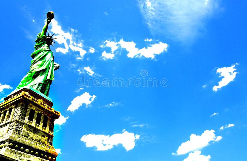 Statue of liberty under a clear sky. Statue of liberty under a shining clear sky with white clouds royalty free stock photography