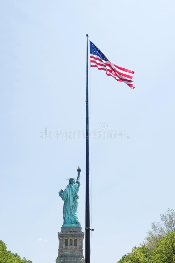 Statue of Liberty and USA flag, New York City, USA royalty free stock image