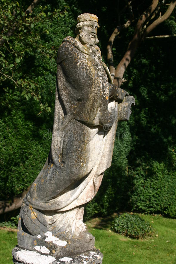 Statue with lichens. Statue of a man covered with lichens on a plinth with grass and trees as background stock photo