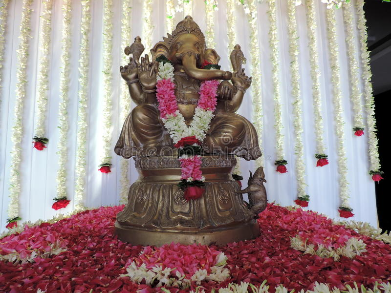Statue of Lord Ganesha, decorated with flowers. Ganesha, also known as Ganapati and Vinayaka, is one of the best-known and most worshiped deities in the Hindu stock image