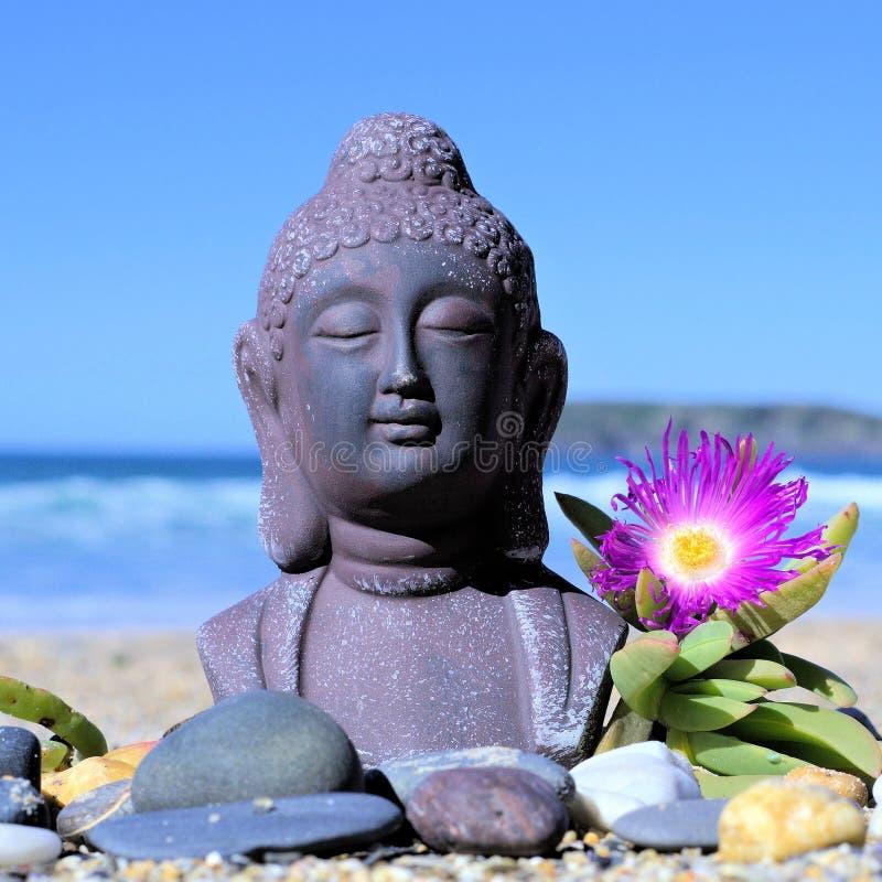 Statue méditante de Bouddha sur le sable image stock