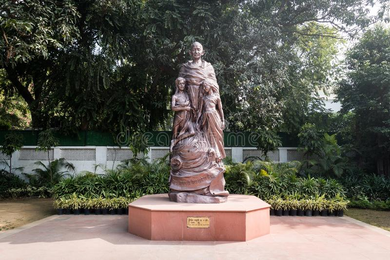 The statue of Mahatma Gandhi with children in bronze standing in the courtyard royalty free stock photography